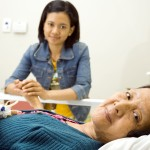 sick asian grandmother seems happy visited by her granddaughter. having bed resting in inpatient treatment at the hospital